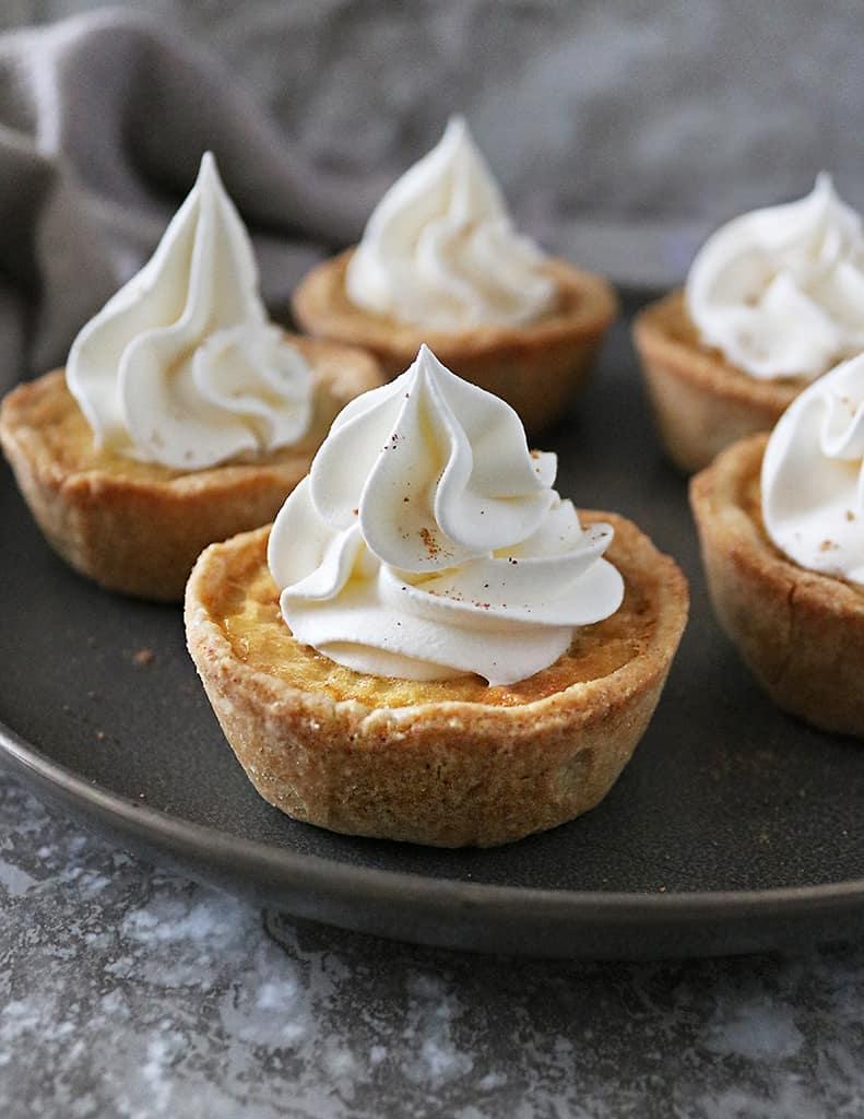 Tasty indulgent egg custard tarts with whipped cream