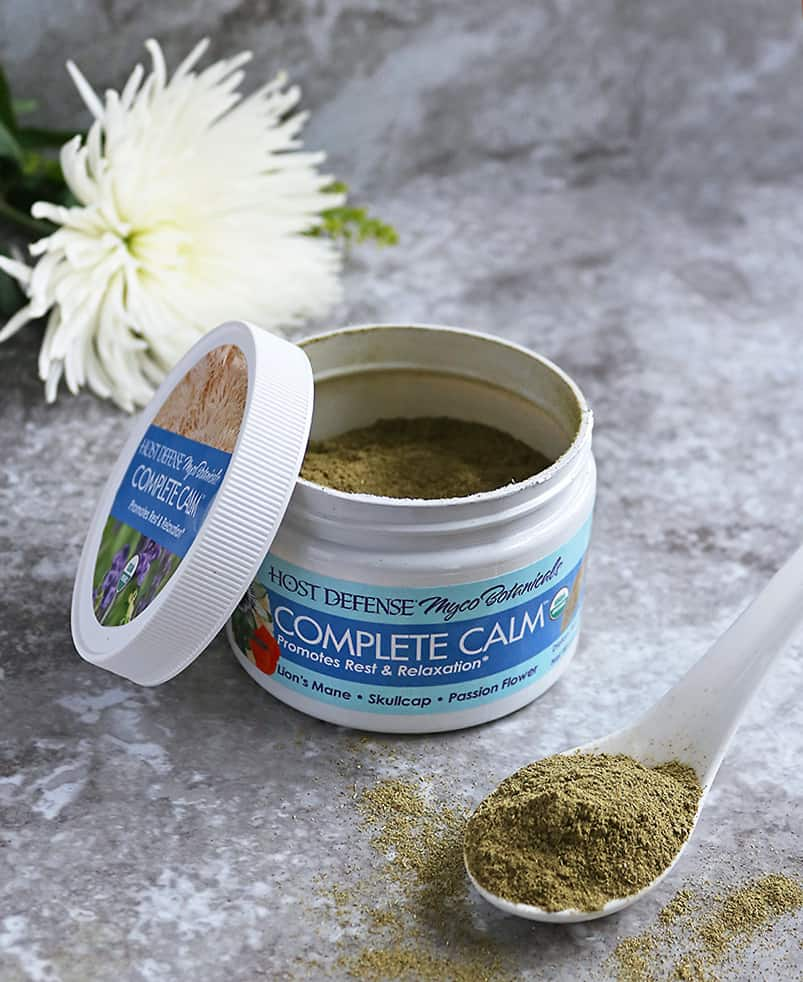 Host Defense Complete Calm Powder  with a flower in background