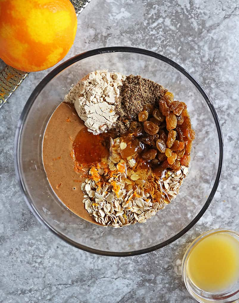 Ingredients to make Orange Protein Energy Balls in a glass bowl.