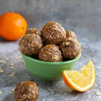 Green bowl with Orange Protein Energy Balls in it.