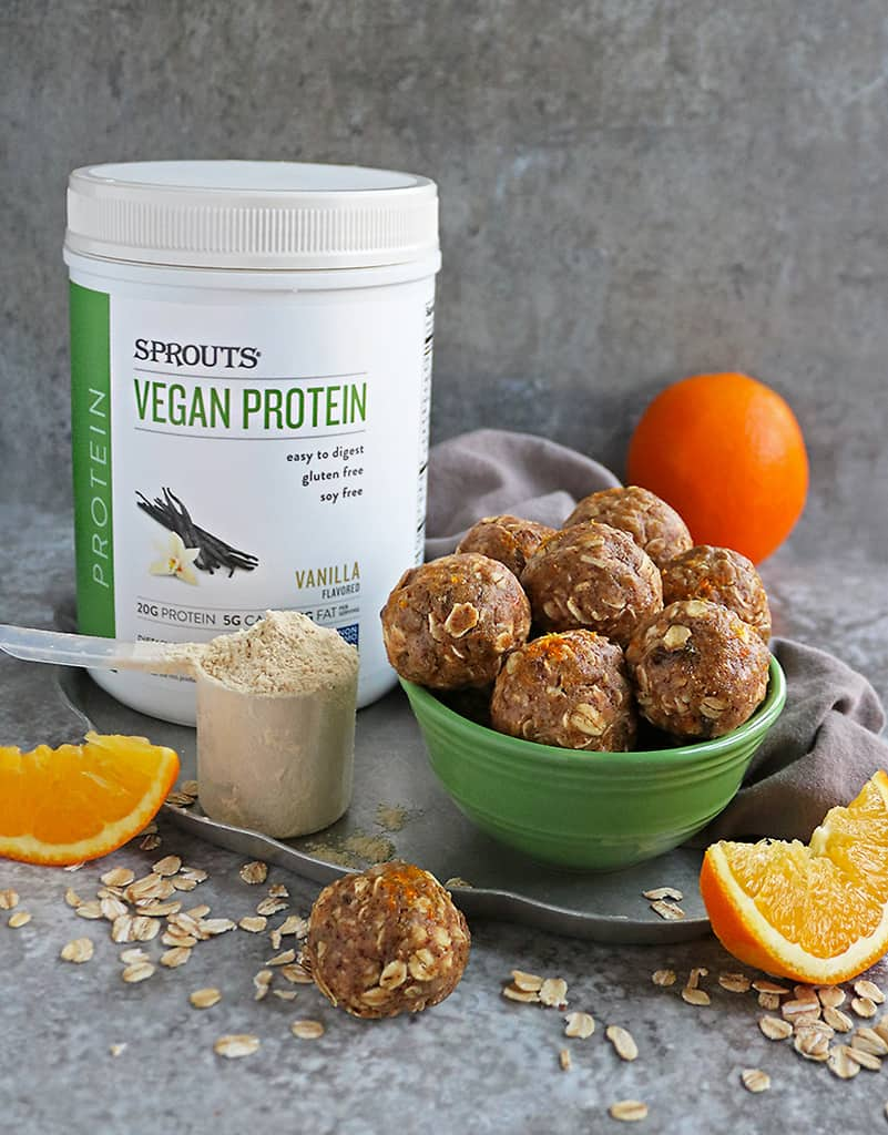 Orange Protein Energy Balls in a bowl with Sprouts Vegan Protein in the background