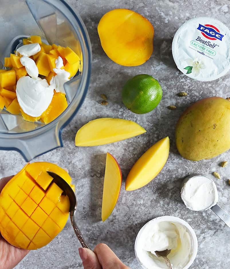 scooping out mango to place in the blender while being surrounded by the ingredients to make mango lassi.