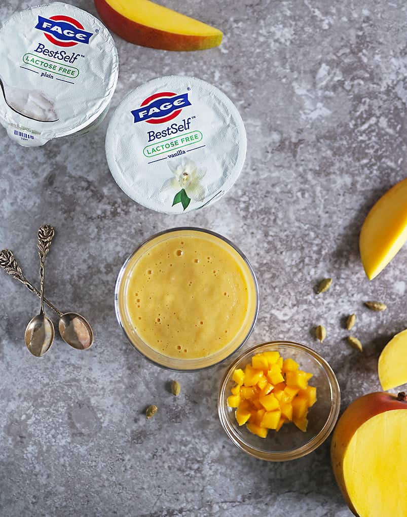 overhead photo of 2 containers of FAGE along with a glass of mango lassi and a bowl with chunks of mango