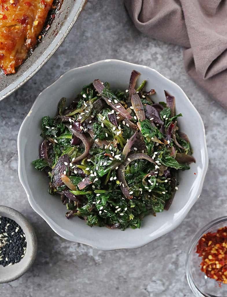 a gray bowl with Sauteed Soy Sesame Spinach & Onions