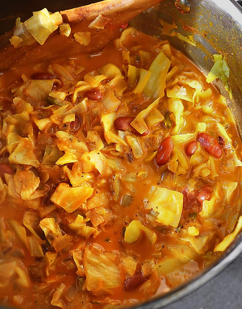 Tender cabbage cooking in a saucepan with a delicious tomato coconut broth