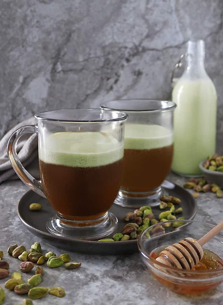 Add in strong brewed coffee to frothed pistachio milk and honey in mug