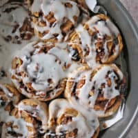 Baking tray with just iced cinnamon rolls.