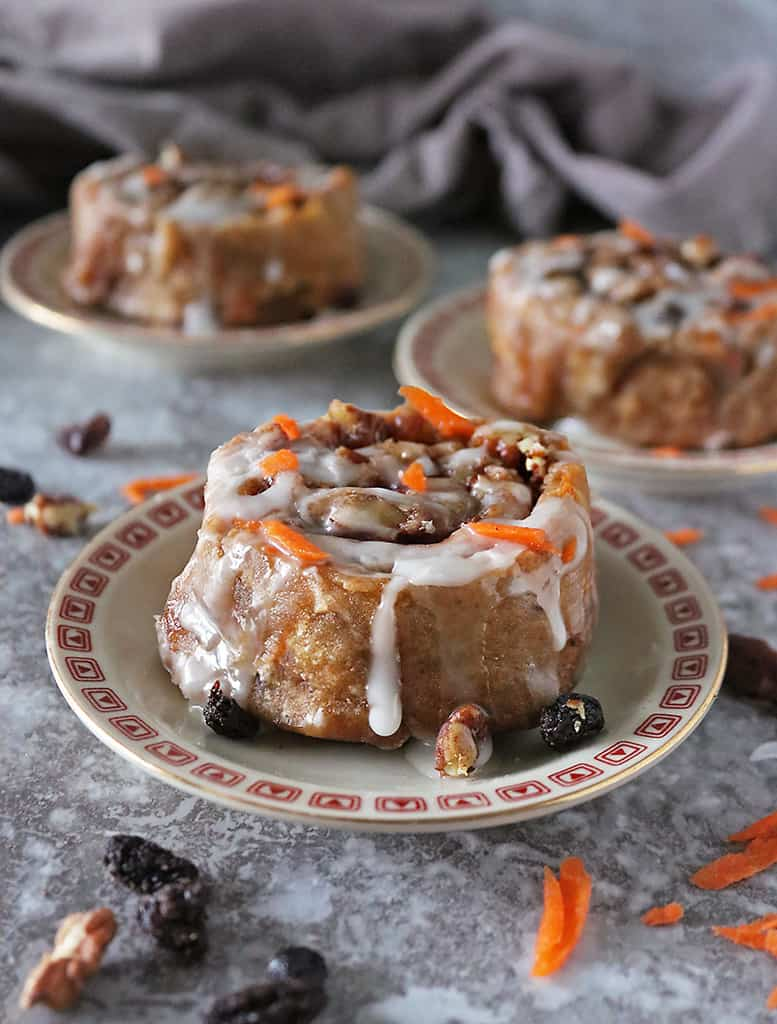 One carrot cake cinnamon roll on a plate with two others in the background