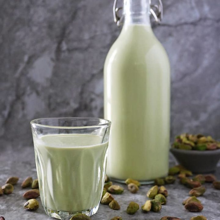 A bottle and a glass cup of Easy plant-based - clean keto Pistachio milk