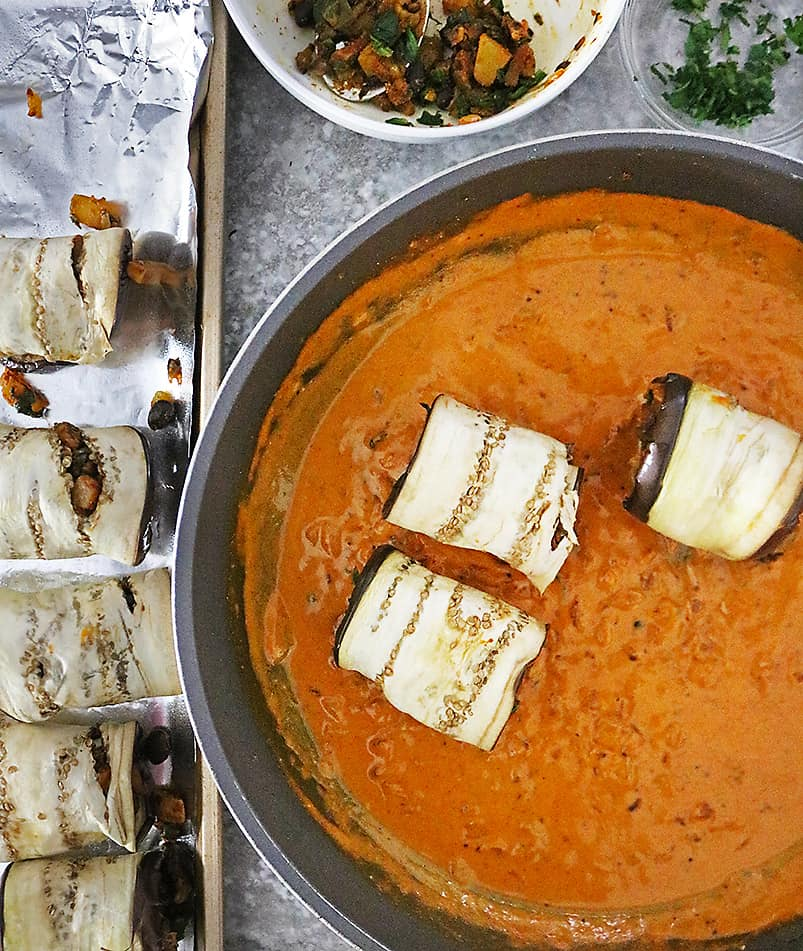 Placing stuffed eggplant slices in rich spicy sauce