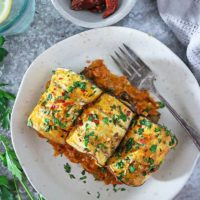 Three plant-based potato and bean stuffed eggplant rollatini on a plate.
