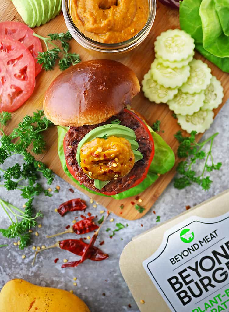 overhead photo of pen faced Delicious plant based Beyond Meat Burger with spicy mango sauce and fixings