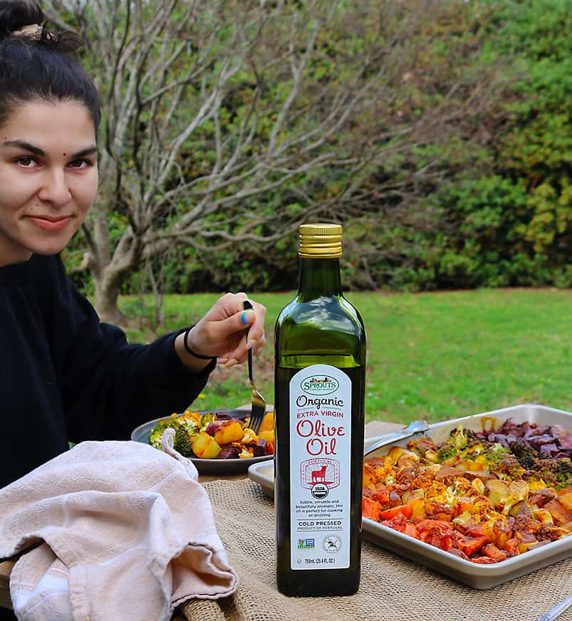 photo of Geri enjoying Earth Day And Sprouts Organic Extra Virgin Olive Oil on a rainbow of roasted veggies in our backyard.