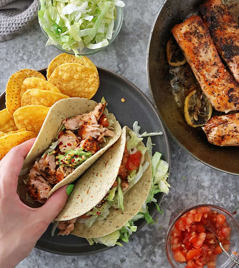 Hand reaching to grab a taco from a plate of two tacos with chips, salmon, lettuce, tomatoes, and gauc on the side.