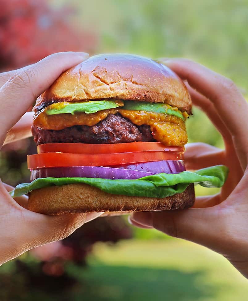 Taking a bite of plant-based Beyond Meat Burger with spicy mango sauce