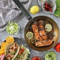 flaky delicious lemon ginger salmon in tacos with gauc and tomatoes