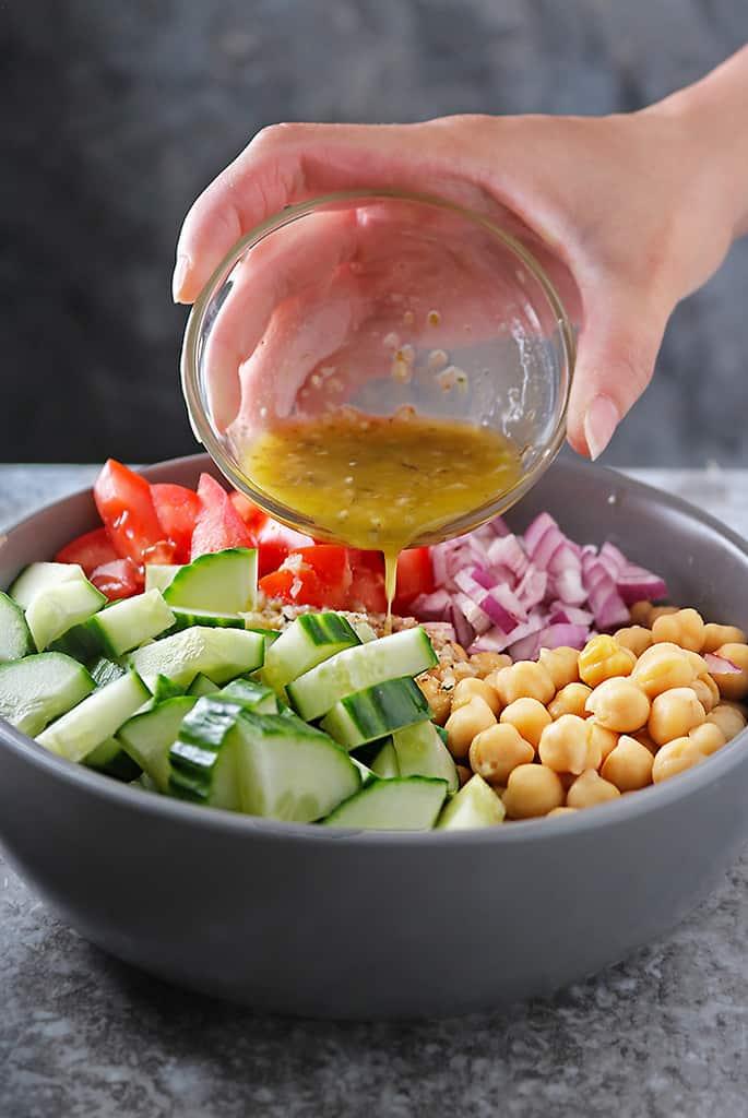 Pouring over Garlic Vinaigrette onto easy chickpea salad