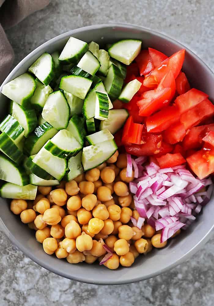 Prepping veggies to make vegan chickpea salad in a large grey bowl