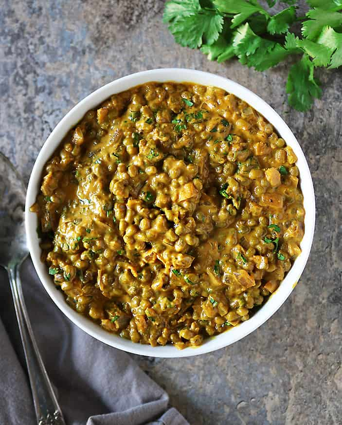 A large bowl of easy vegan moong bean curry on a marble background.