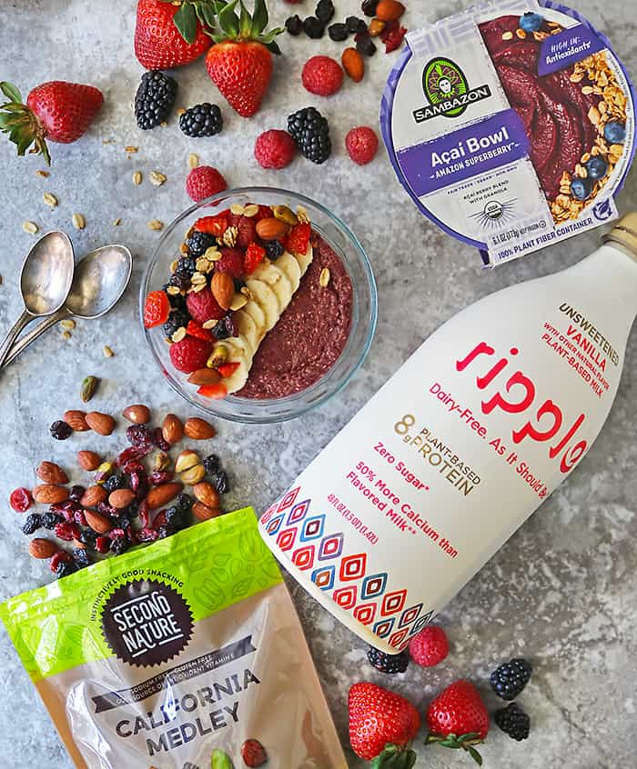 delicious easy creamy acai chia pudding in a glass bowl with the ingredients needed to make it lying around it.