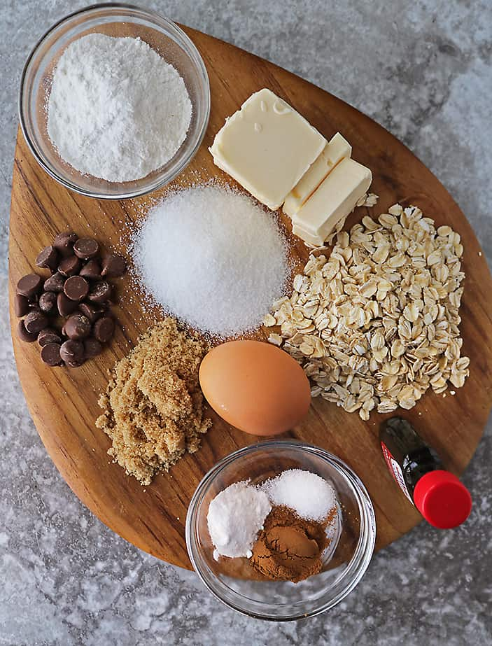 12 ingredients to make oatmeal cookies gluten-free on a cutting board.