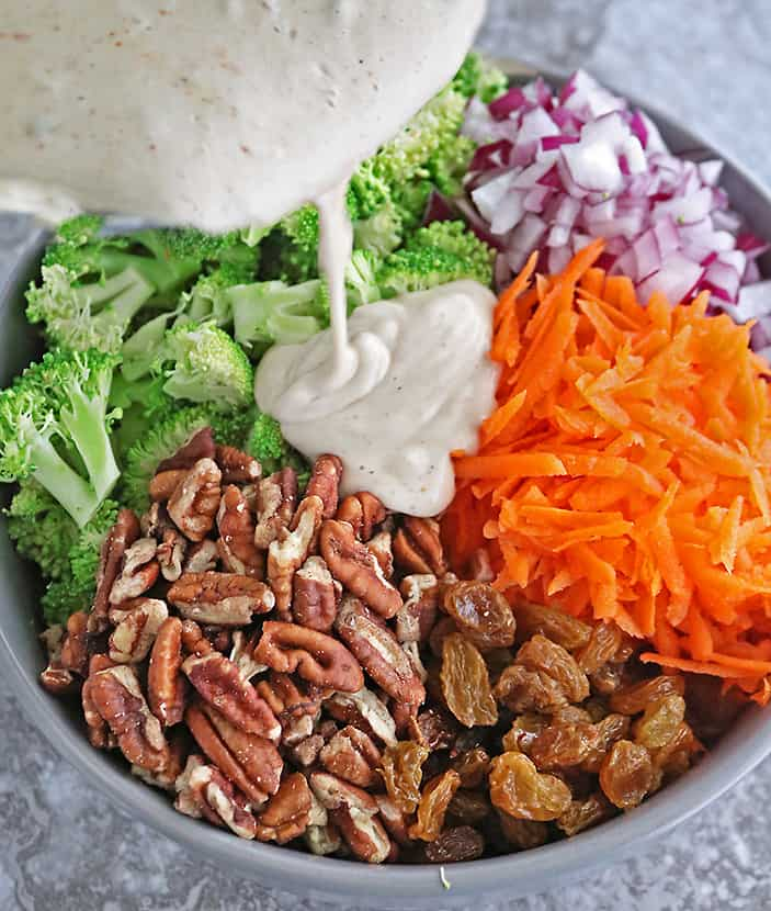 Adding cashew cream sauce to other-ingredients for broccoli salad