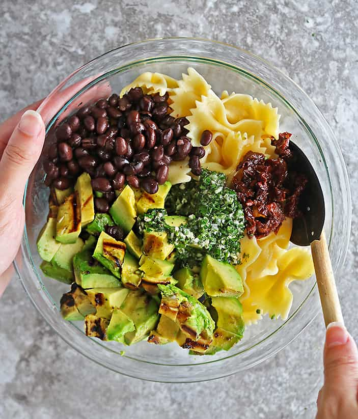 Overhead photo of a hand mixing together the ingredients to make this healthy pasta salad.