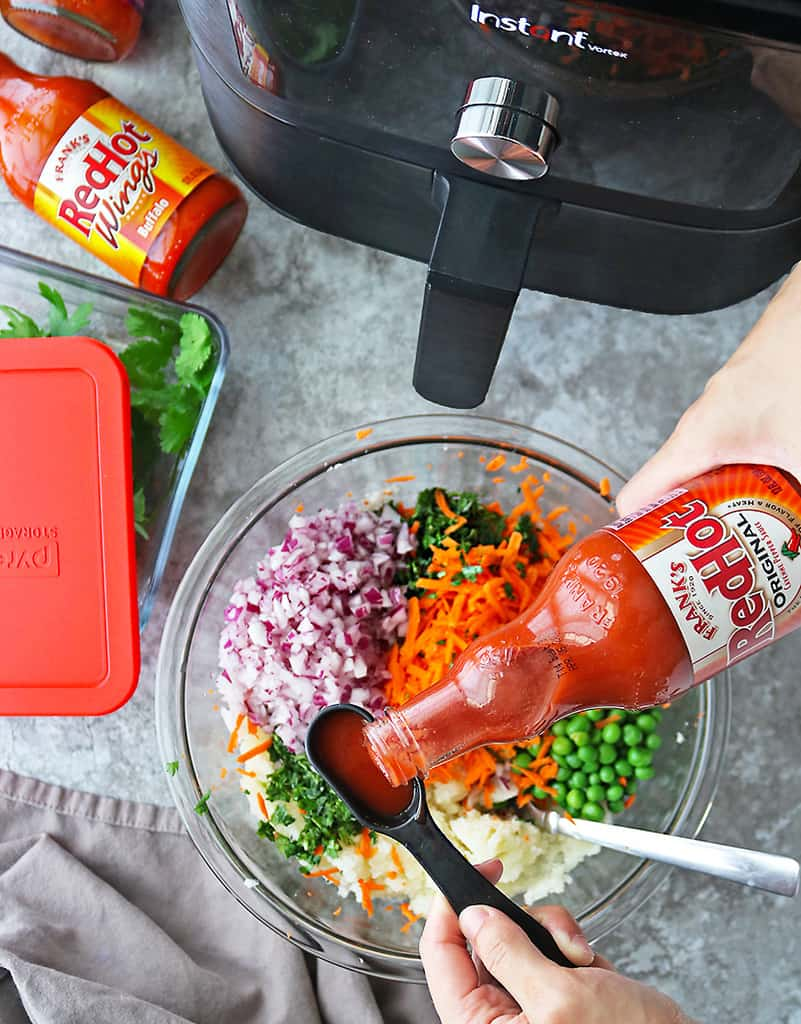 Photo showing the addition of Franks RedHot to the ingredients to make spicy veggie fritters.