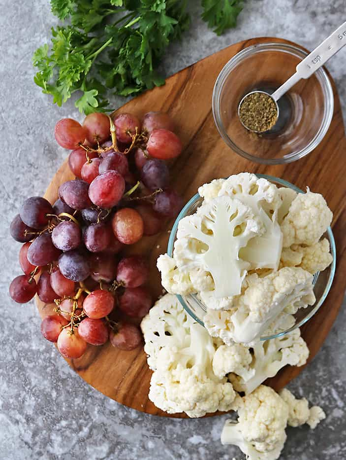 Ingredients to make roasted cauliflower and grapes on a wooden cutting tray.