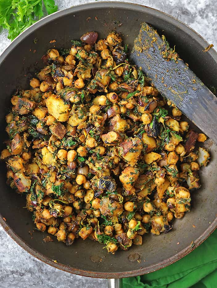 Sauteing together potatoes, chickpeas, spinach, ginger, garlic, onion, and spices to make a wholesome nutritious and flavorful dish that is satisfying and so tasty.