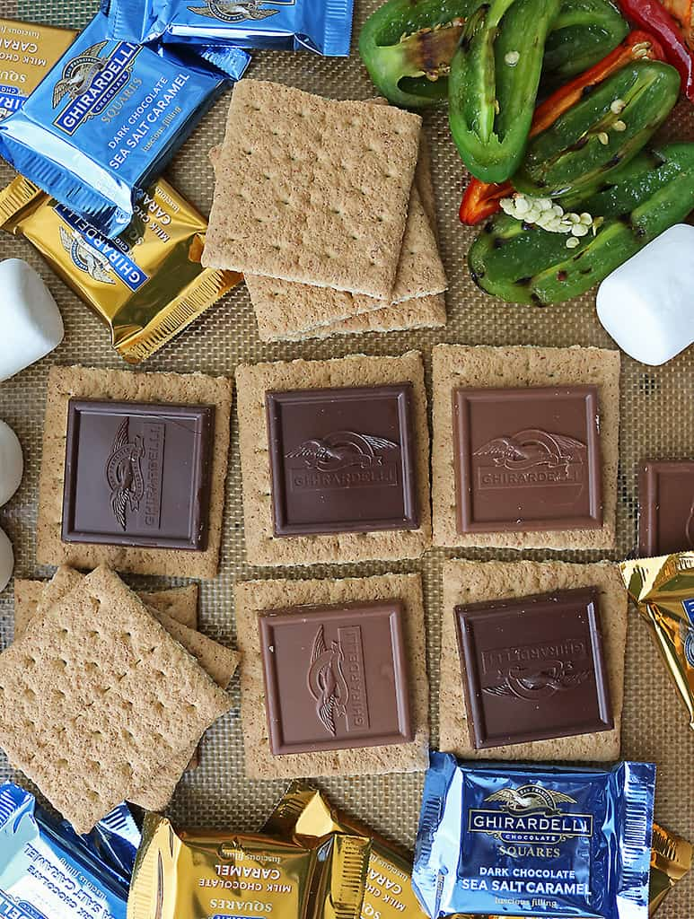 Adding graham crackers, chocolate squares to baking tray to make baked s'mores.