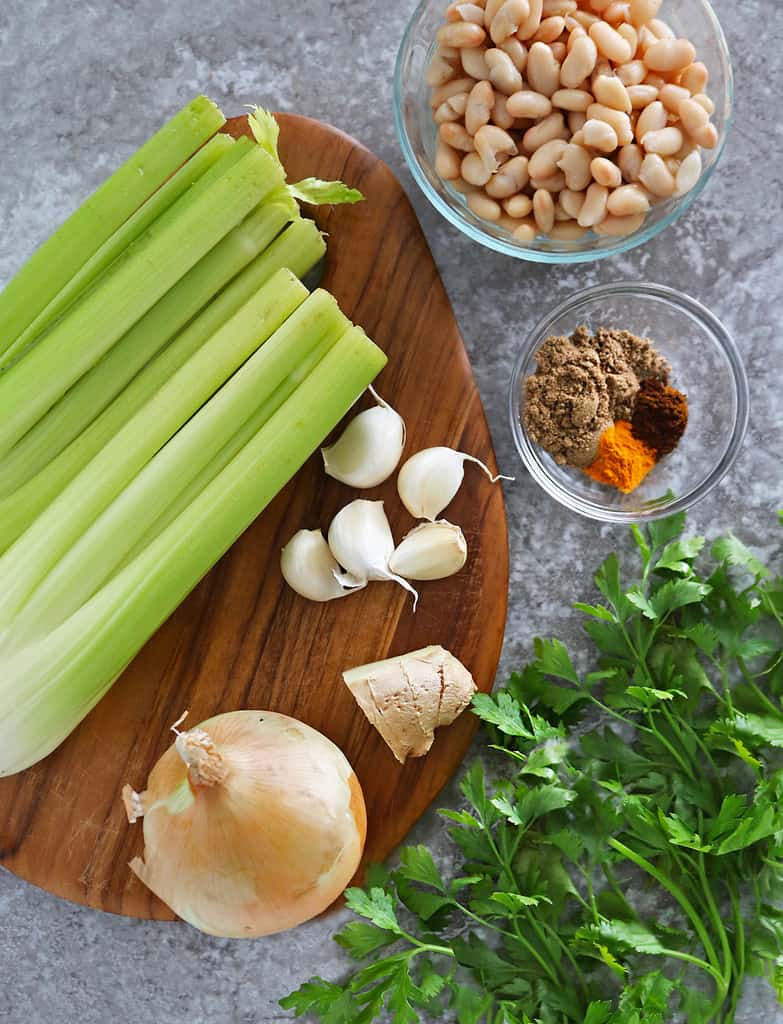 10 ingredients needed to make celery soup laid out on a cutting board on a grey background.