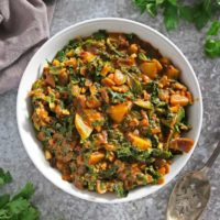 A big bowl of easy kale curry with potatoes on a gray background.