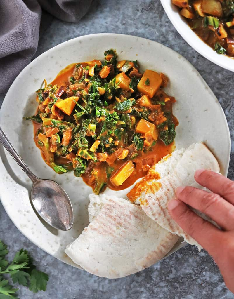 Digging into a plate of kale curry with pita bread