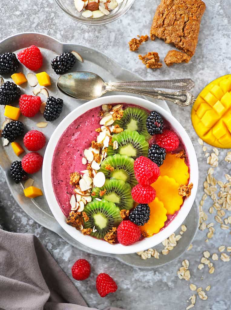 Easy Berry Oatmeal Smoothie Bowl with kiwi, mango, berries on top.
