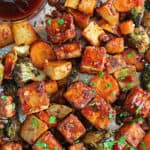 Tofu is spiced and oven roasted until crispy, along with a medley of comforting vegetables in this Easy Sheet Pan Spicy Tofu dish.