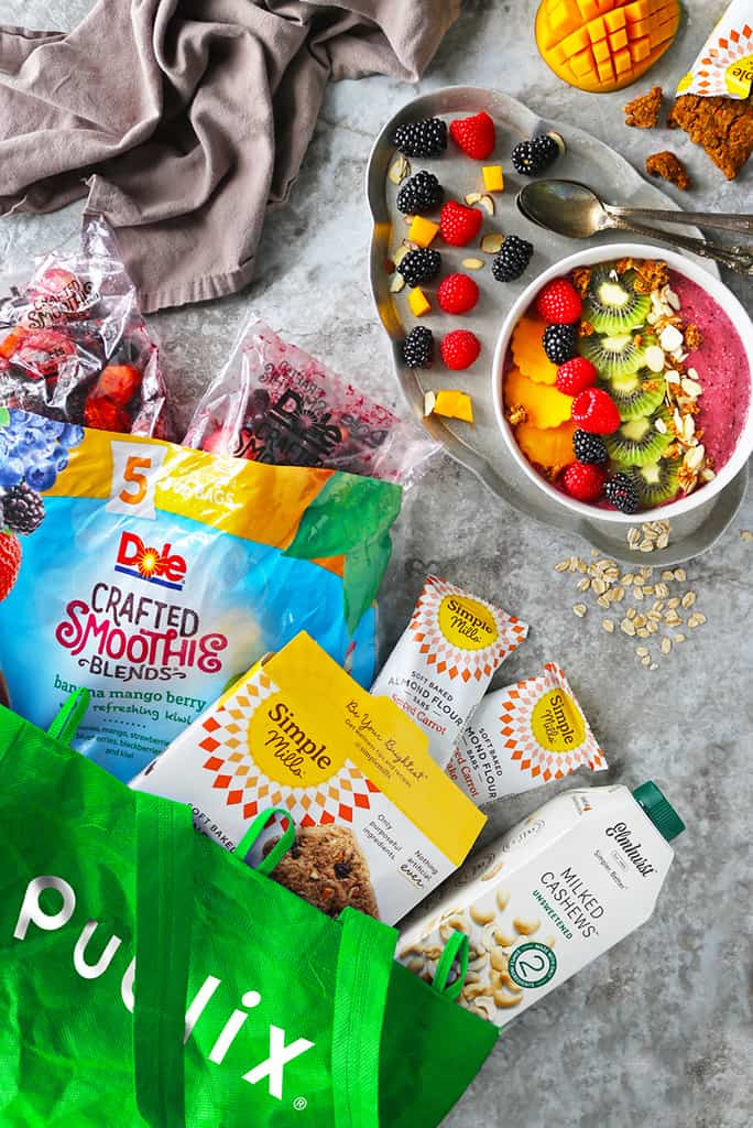 An oatmeal smoothie bowl is in a bowl and it is topped with colorful fruits. Next to it is a publix bag with ingredients used to make this oatmeal smoothie bowl.