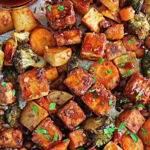 The most crispy Easy Sheet Pan Spicy Tofu and veggies on a sheet pan with BBQ sauce.