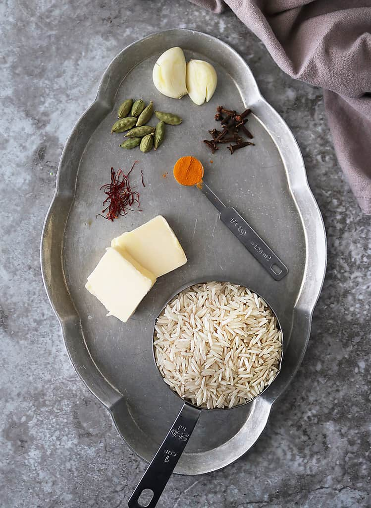 The 7 ingredients needed to make this yellow rice on a grey platter.