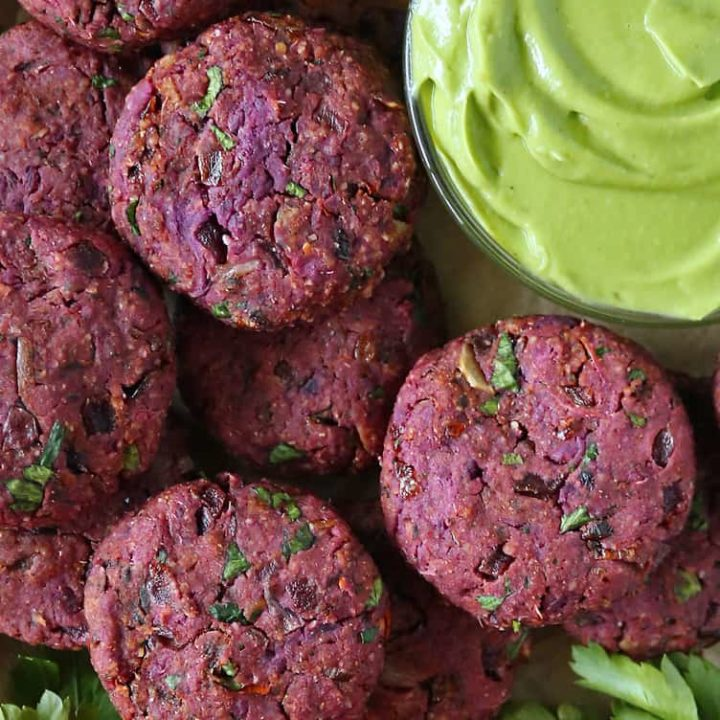 A tray with harissa spiced purple sweet potato fritters .