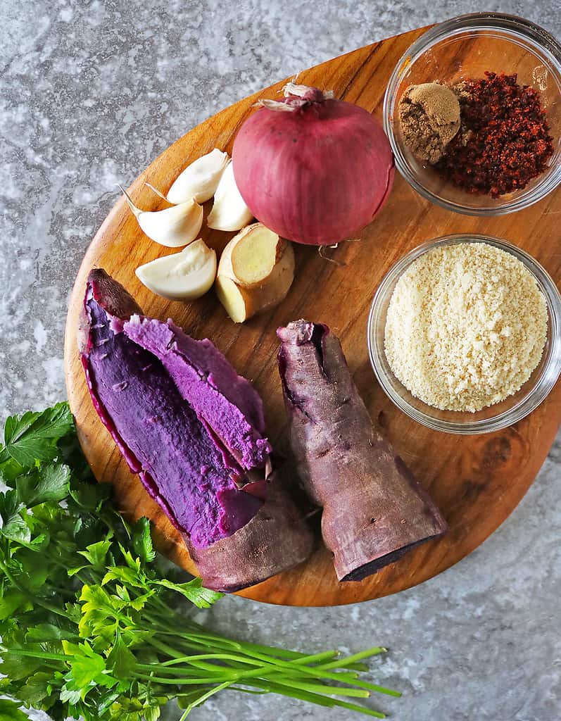Ingredients to make purple sweet potato fritters aka one-eyed purple people eater on a wooden board.