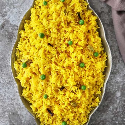 A big gray tray with Yellow rice with cardamom and cloves.